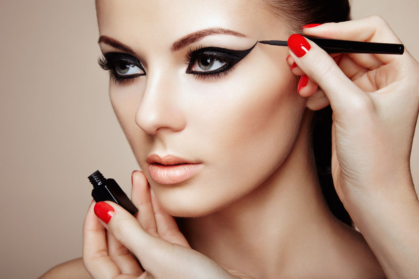 Rostro de mujer maquillada y manos aplícandole maquillaje en los ojos,