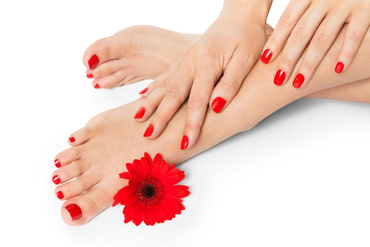 Pies y manos de mujer con una bonita manicura y pedicura con uñas de color rojo