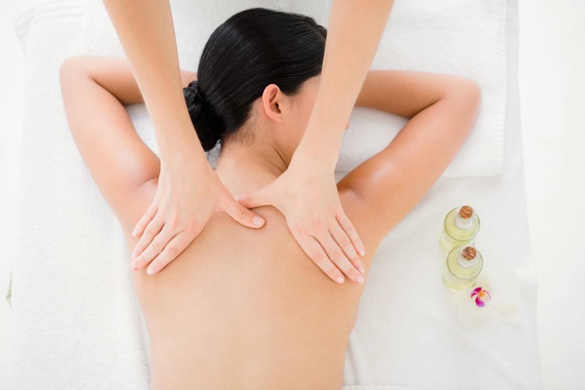 Mujer tumbada boca abajo dándose un masaje en la espalda